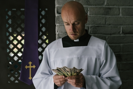 Catholic priest counting money in his hand. Church and money