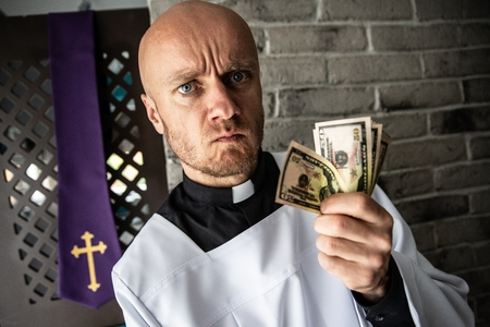 Catholic priest with money in his hand. Church and money
