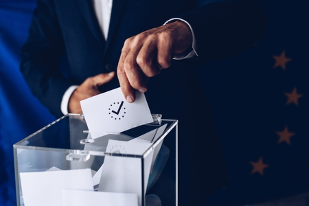 EU elections. Man throwing his vote into the ballot box. Elections to the European Parliament Banco de Imagens