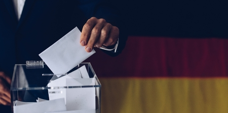 Elections in Germany. Man throwing his vote into the ballot box. German flag in the background. Stockfoto
