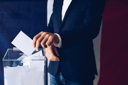 Elections in France. Man throwing his vote into the ballot box. French flag in the background.