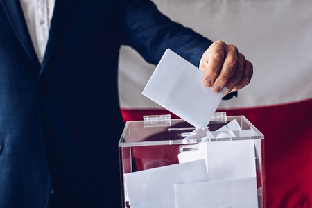 Elections to the Polish Parliament. Man throwing his vote into the ballot box. Polish flag in the background Banco de Imagens