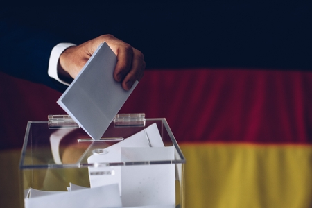Elections in Germany. Man throwing his vote into the ballot box. German flag in the background. Banco de Imagens