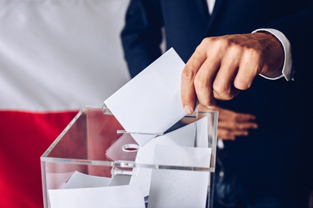 Man throwing his vote into the ballot box. Polish flag in the background. Elections to the Polish Parliament.