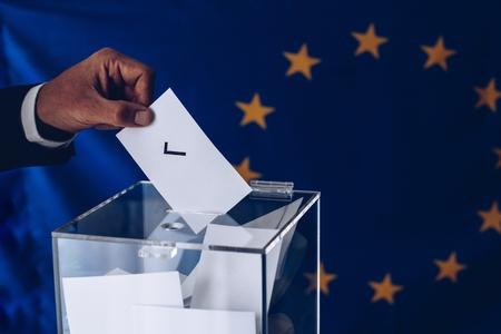 European Union elections. Man inserting his vote to ballot box.