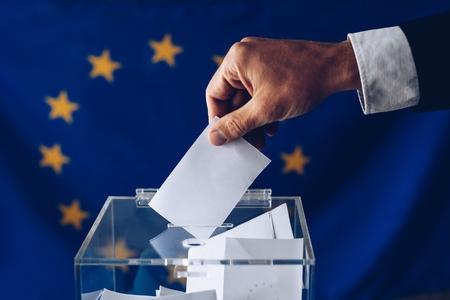 Man inserting his vote to ballot box. European Union elections