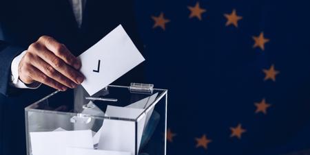 Male inserting his vote to ballot box. European Union elections