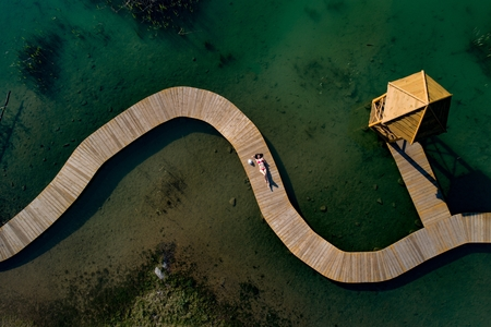 Aerial drone view woman in swimsuit sunbathing on the pier. Female relaxing on vacations
