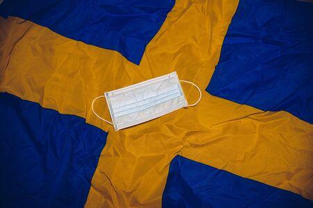 Medical protective mask on Sweden flag. Coronavirus in Sweden. Stockfoto