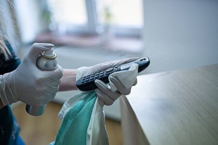 Woman disinfects the phone with a spray disinfectant liquid.