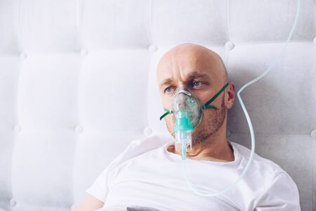 Man breathing through oxygen mask in bed. Covid-19 patient.