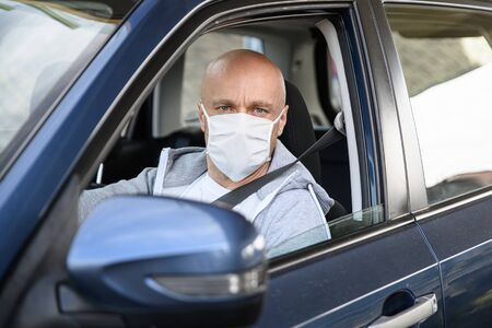 Man driving a car in medical protective mask. Archivio Fotografico