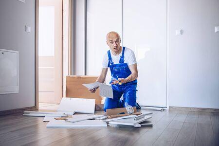 Nervous confused man assembling cabinet at home.