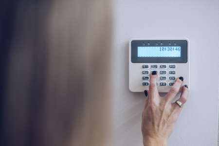 Security home system. Woman entering secret code on home alarm