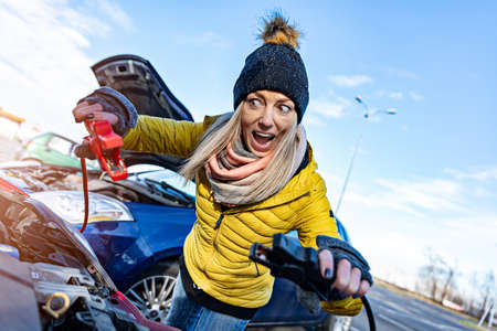 A terrified, furious blonde woman in a yellow jacket tries to recharge the discharged battery.