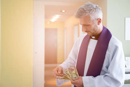 Catholic cleric priest counting american money dollar.