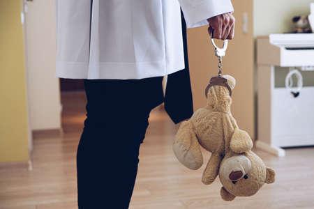 Priest holding child plush toy teddy bear Stock Photo
