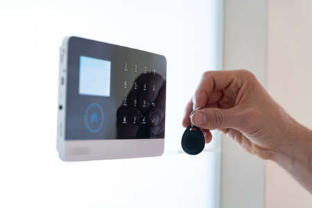 Hand of an adult male uses a home alarm remote control.
