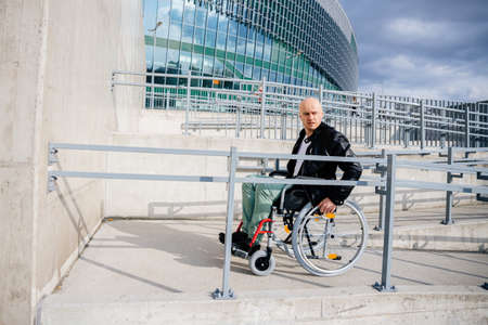 A disabled man rides a wheelchair up a ramp for the disabled.