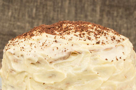 Cake with white cream and chocolate powder on wood background