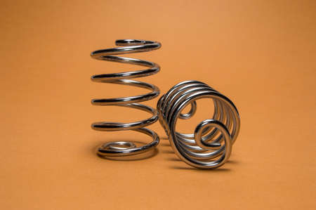 two metal steel springs on brown background Stock Photo