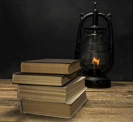 oil lamp: book and kerosene lamp on the wooden table