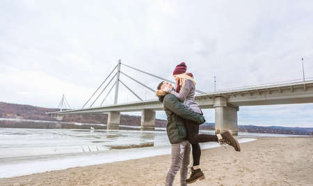 Beautiful young couple hugging next to bridge Stock Photo