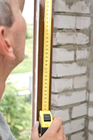 measures:  Man measures window