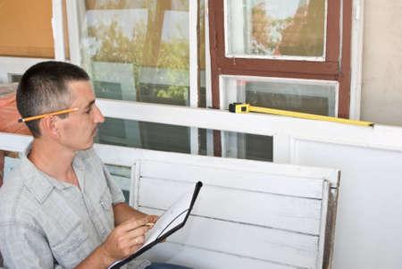 window repair: Man measures window Stock Photo