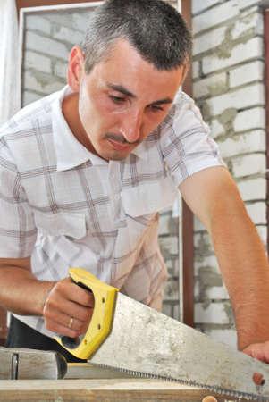 un carpintero aserrando un tablón Foto de archivo - 5160442