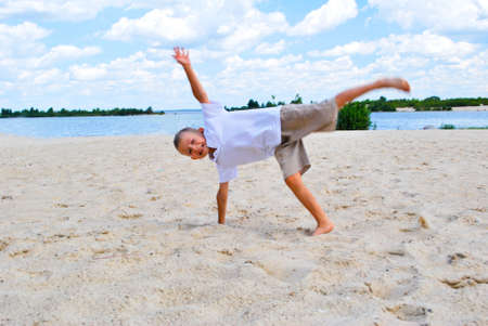 topsyturvy: somersault boy on the beach Stock Photo