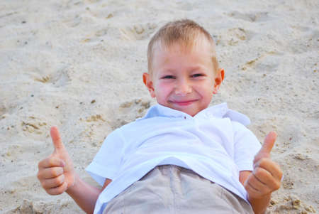 Portrait of little boy showing thumbs up sign photo