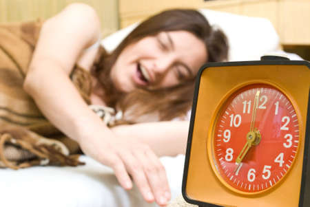 snoozing: Young woman snoozing a red alarm clock