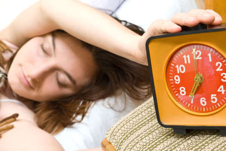Young woman snoozing a red alarm clock photo