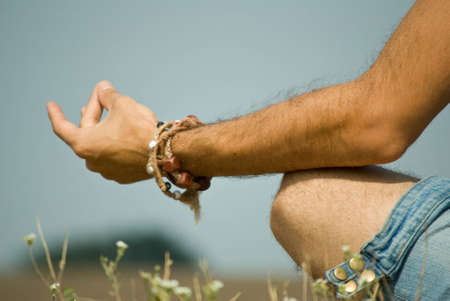 Close up of man's hand resting on her knee with fingers in meditation pose. Stock Photo - 7725739