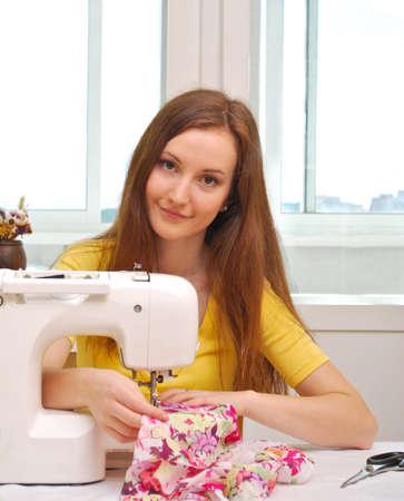 hem: Woman seamstress work on the sewing-machine