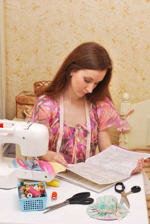Woman seamstress work on the sewing-machine photo