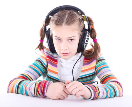 Happy little girl in headphones listens to music photo