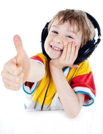 Portrait of a sweet young boy listening to music on headphones against white background photo