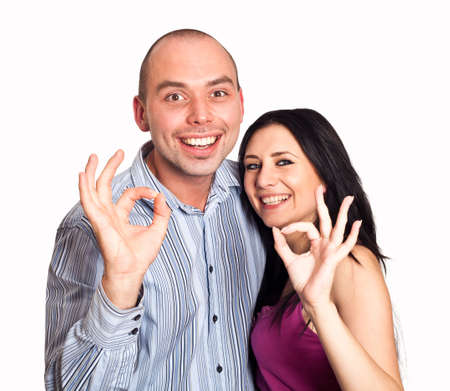 Closeup of good looking young couple gesturing okay sign over white background photo