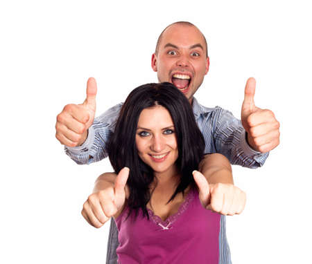 Two young smiling people with thumbs-up gesture isolated on white