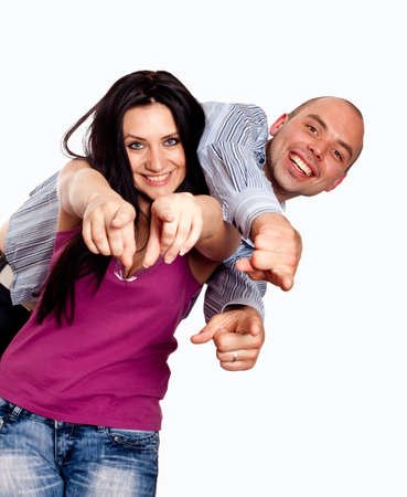 Portrait of happy young couple pointing at you over white background photo