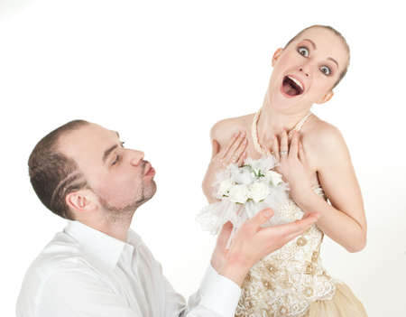 Beautiful  wedding couple - groom and surprised bride over white background photo