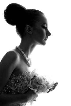 Silhouette of the bride weared in dress over white background photo