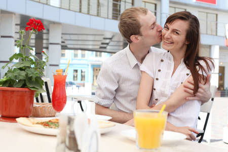 Portrait of  young man kissing his girlfriend in cafe photo
