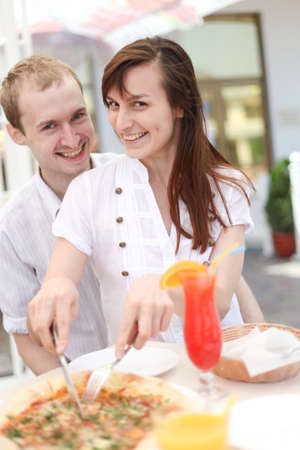 Young couple cutting pizza in cafe photo
