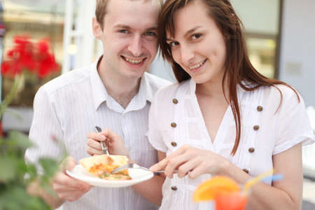 Young couple eating pizza in cafe photo