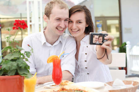 A young  couple  taking their photo on a digital camera in cafe photo