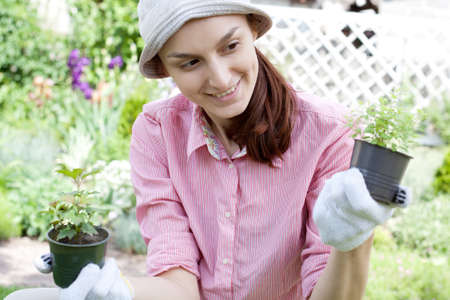 Smiling woman with herbs in garden photo