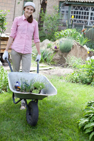Portrait of woman with wheelbarrow in the garden photo